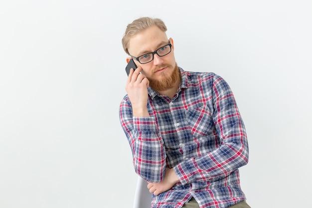 Brodaty przystojny mężczyzna rozmawia przez telefon na białej powierzchni