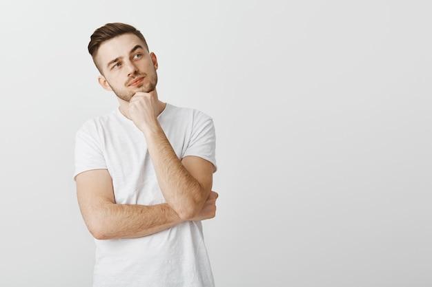 Brodaty przystojny młody człowiek myśli, dokonując wyboru w sklepie, patrząc w prawym górnym rogu