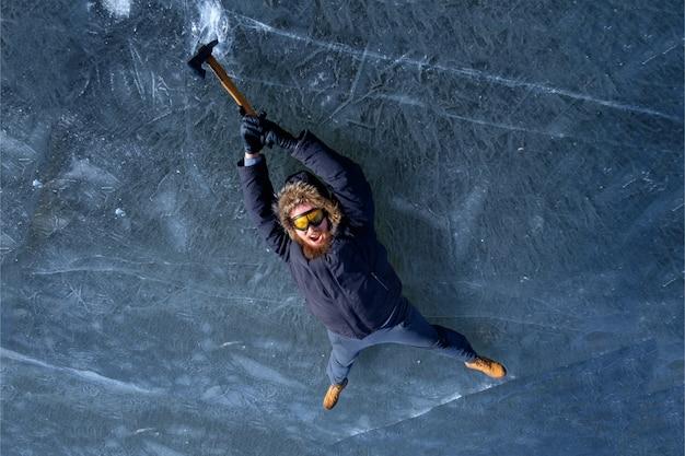 Brodaty rudy alpinista w żółtych szklankach ochronnych z toporem lodowym zawieszonym na lodowatej skale