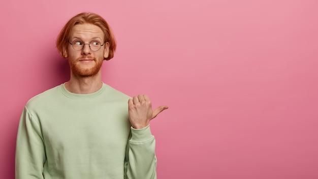 Brodaty rudy dorosły mężczyzna wskazuje kciukiem na prawą stronę