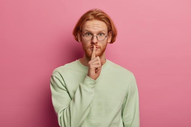 Brodaty rudy mężczyzna robi gest cicho, trzyma palec wskazujący na ustach