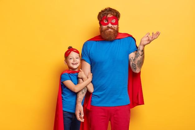Brodaty rudy ojciec patrzy zmieszany, unosi wytatuowane ramię