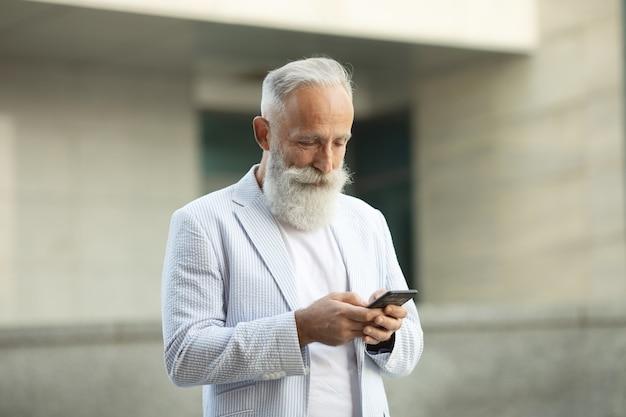 Brodaty starszy biznesmen uśmiechający się stojąc na zewnątrz i czytając swój telefon komórkowy