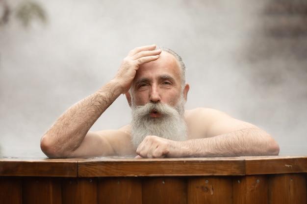 Brodaty starszy mężczyzna korzystających z kąpieli termalnych w centrum talasoterapii.