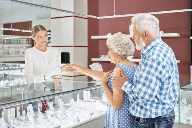 Brodaty starszy mężczyzna robi luksusowy prezent swojej ukochanej kobiecie