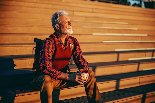 Brodaty starszy mężczyzna siedzi na schodach na zewnątrz, patrząc na coś i pije kawę na wynos.