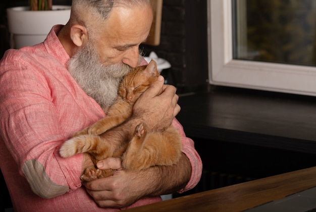 Brodaty starszy mężczyzna trzyma ślicznego kota w domu.