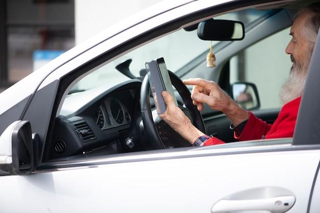 Brodaty starszy mężczyzna trzymający telefon i wysyłający sms-y siedząc w samochodzie na parkingu