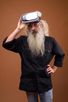Brodaty starszy mężczyzna używający okularów vr do wirtualnej rzeczywistości
