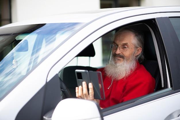 Brodaty starszy mężczyzna w okularach trzymający telefon i wysyłający sms-y siedząc w samochodzie na parkingu