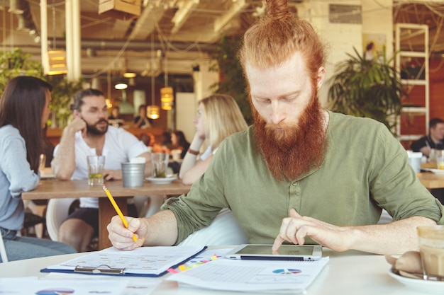 Brodaty student pracuje na papierze kursowym, prowadzi badania, analizuje statystyki na tablecie, zapisuje w notatniku ołówkiem.