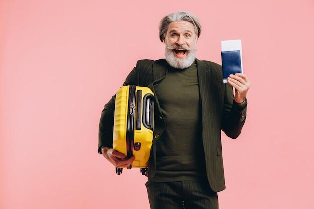 Brodaty stylowy mężczyzna w średnim wieku z żółtą walizką i paszportem z różowym biletem.