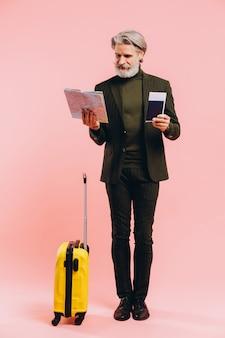 Brodaty stylowy mężczyzna w średnim wieku z żółtą walizką, mapą i paszportem z różowym biletem.