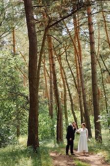 Brodaty, stylowy pan młody w garniturze i piękna blondynka panna młoda w białej sukni z bukietem w dłoniach stoją i przytulają się na łonie natury w sosnowym lesie.