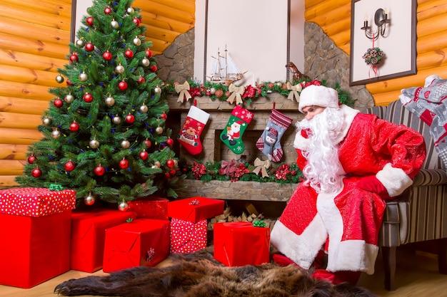 Brodaty święty mikołaj siedzi na krześle, pudełka na prezenty, kominek i udekorowana choinka