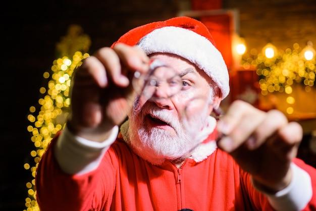 Brodaty święty mikołaj w okularach w rękach świąteczna dekoracja szczęśliwego nowego roku prezent optyki świętego mikołaja