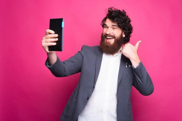 Brodaty szczęśliwy mężczyzna biorąc selfie z podkładką