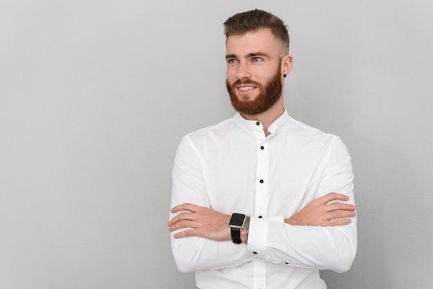 Brodaty szczęśliwy mężczyzna uśmiechający się z rękami skrzyżowanymi na białym tle nad szarą ścianą