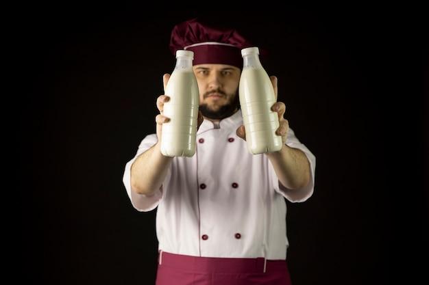 Brodaty szef kuchni mężczyzna w mundurze posiada dwie butelki mleka, skupić się na mleku