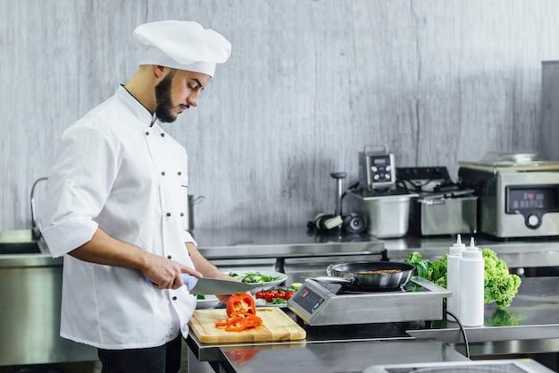 Brodaty szef kuchni przygotowuje świeżą rybę łososiową, krojenie czerwonej papryki