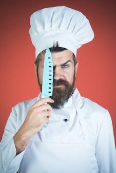 Brodaty szef kuchni trzyma nóż obok twarzy. poważny brodaty kucharz z niebieskim nożem w ręku. na białym tle na czerwonym tle. koncepcja kucharza i przygotowania. reklama w restauracjach. gotowanie.