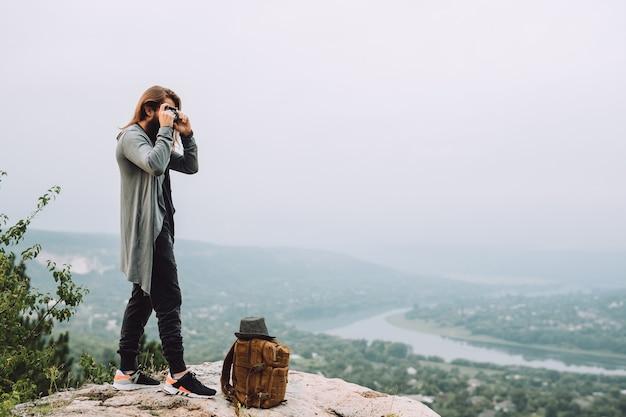 Brodaty turysta robi zdjęcie pięknego krajobrazu.