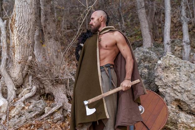 Brodaty wiking z ogoloną głową stoi ubrany w skórę zwierzęcia trzymającego w ręku topór bojowy