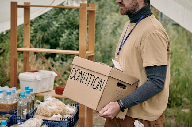 Brodaty wolontariusz z odznaką niesie karton z darowizną na stół z towarami dla bezdomnych