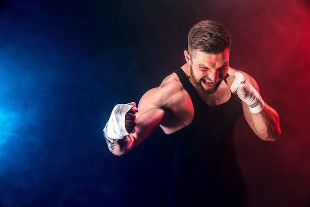 Brodaty wytatuowany bokser muay thai na czarnym tle w czarnym podkoszulku i rękawicach bokserskich walczący na ciemnym tle z dymem. koncepcja sportu.