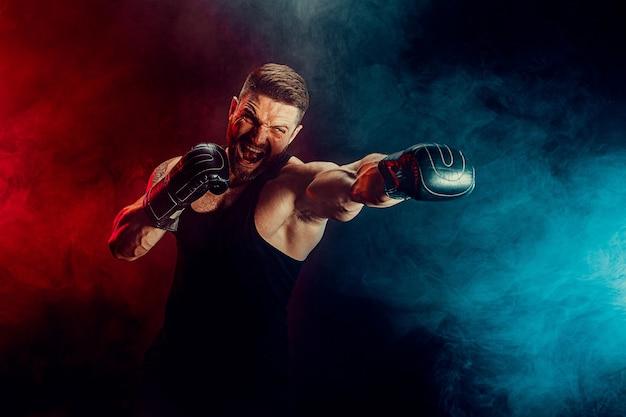 Brodaty wytatuowany sportowiec muay thai bokser w czarnym podkoszulku i rękawicach bokserskich walczący na ciemnej ścianie z dymem. koncepcja sportu.