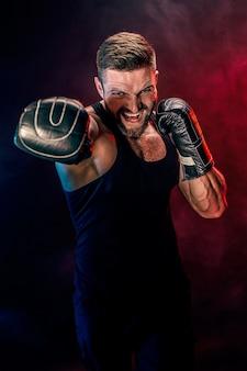 Brodaty wytatuowany sportowiec muay thai bokser w czarnym podkoszulku i rękawicach bokserskich walczący na ciemnym tle z dymem. koncepcja sportu.