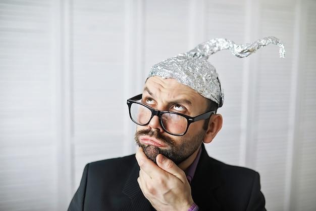 Brodaty Zabawny Mężczyzna W Czapce Z Folii Aluminiowej. Fobie Koncepcyjne. Teoria Spiskowa. Spisek. Niepoczytalność. Premium Zdjęcia
