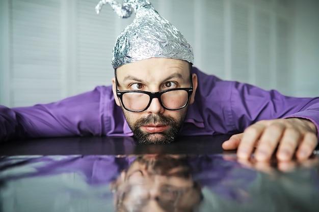 Brodaty zabawny mężczyzna w czapce z folii aluminiowej. fobie koncepcyjne. teoria spiskowa. spisek. niepoczytalność.
