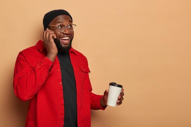 Brodaty zadowolony młody człowiek rozmawia przez telefon z najlepszym przyjacielem, trzyma telefon komórkowy