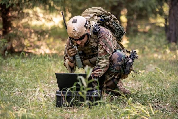 Brodaty żołnierz w mundurze kamuflażowym siedzący w lesie i wysyłający wiadomość przez radio, kontrolując operację wojskową za pomocą komputera