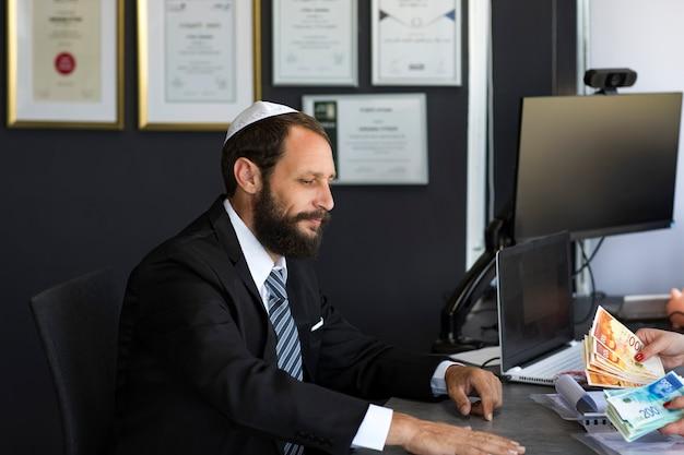 Brodaty żyd w biurze kippah siedzieć z dużą ilością gotówki. pożyczka bankowa lub kredyt. zdobądź gotówkę w kilka minut. koncepcja linii wsparcia bankowego. ręce kobiety liczą izraelskie pieniądze, nowe szekle banknotów