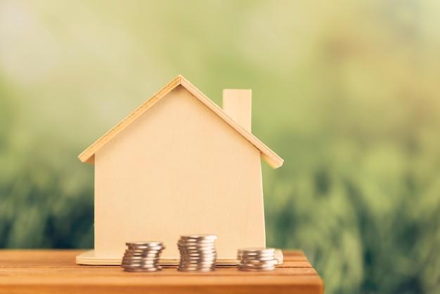 Brogować monety blisko drewnianego domu na stole przy outdoors