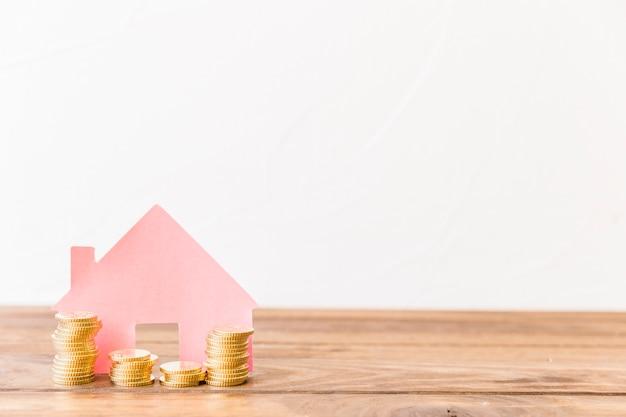 Brogować monety przed domem na drewnianym biurku