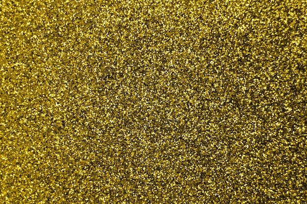 Brokat i flara na złotym błyszczącym modnym tle. cekiny. świąteczne tło dla twoich projektów. niewyraźne złote świąteczne światła bokeh. koncepcja czas świąteczny boże narodzenie na tle.