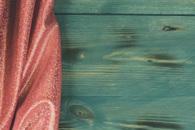 Brokatowe cekiny w kolorze różowym. różowe tło błyszczące tekstury. tkanina w kolorze różowego brokatu i zielona powierzchnia drewna