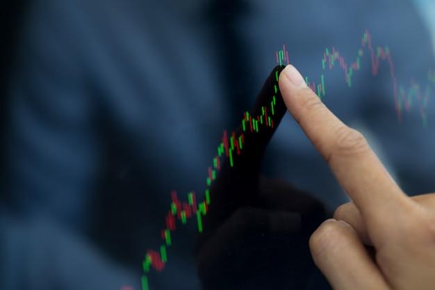 Broker finansowy patrząc na statystyki giełdy i dyskusji na komputerze mo