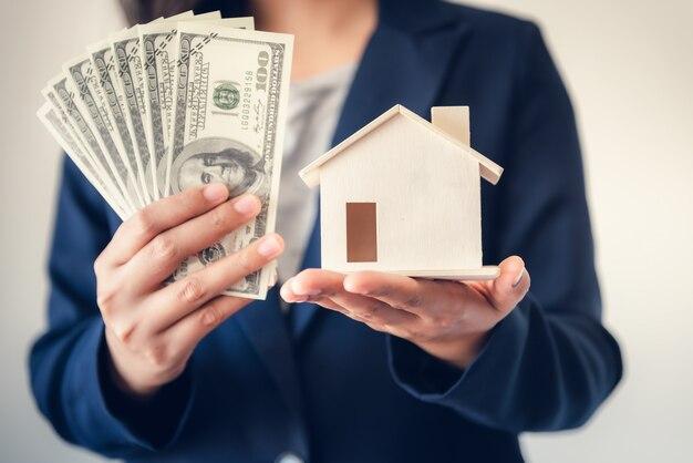 Broker sprzedaje agencję nieruchomości pokazując klientowi pieniądze i model domu.