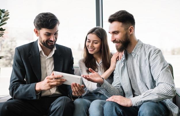 Broker ubezpieczeniowy doradza klientom w biurze. doradca finansowy trzyma cyfrowy tablet, rozmawia z ludźmi, spotyka się, rozdaje