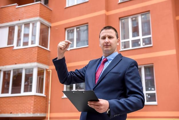 Broker z kluczem z nowego mieszkania w pobliżu nowego domu