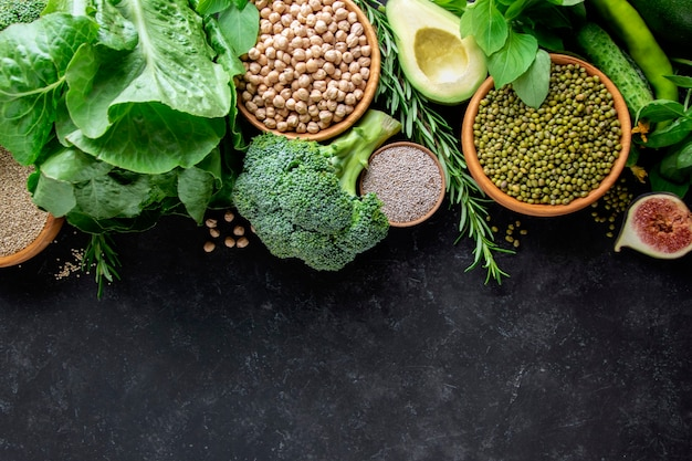 Brokuły, awokado, fasola mung, ciecierzyca, zielenina na czarnym tle, widok z góry. wegański zestaw żywności.