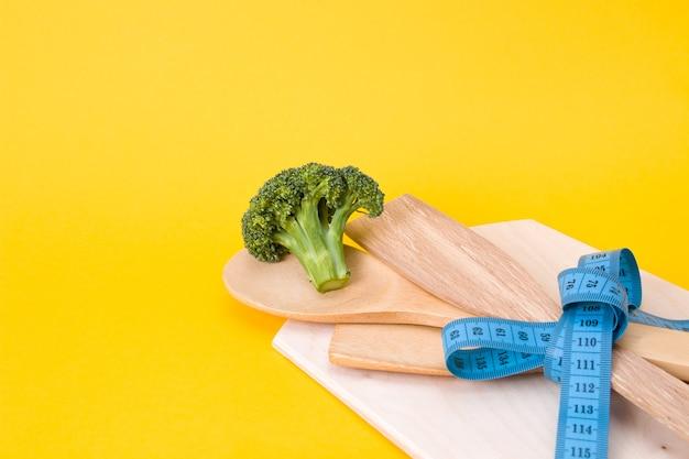 Brokuły, drewniane szpatułki kuchenne z niebieskim tłem taśmy mierniczej, miejsce na kopię, koncepcja diety