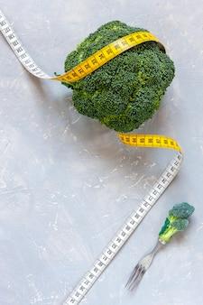 Brokuły i centymetr. świeży egetable, koncepcja odchudzania, dieta, dieta ketogeniczna, przerywany post
