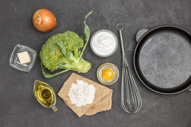 Brokuły i mąka, rozbite jajko w szklanej misce, oliwa, cebula i trzepaczka. patelnia na stole. czarne tło. płaskie ułożenie
