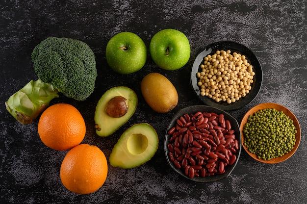 Brokuły, jabłko, pomarańcza, kiwi, rośliny strączkowe i awokado na podłodze z czarnego cementu.