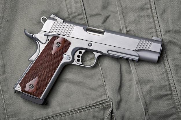 Broń i sprzęt wojskowy dla wojska, półautomatyczny pistolet .45 pistolet na zielonym tle munduru wojskowego.